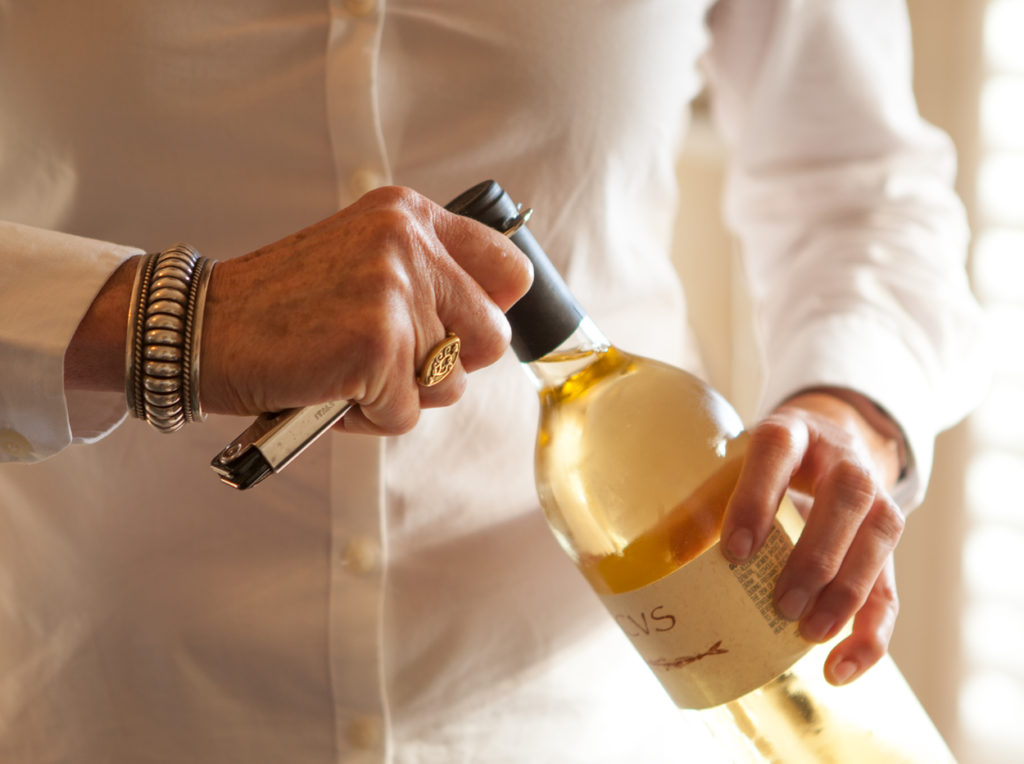 Detail of a guest opening a bottle of white wine.